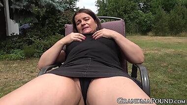 Busty granny dildoes  her self while spreading legs outdoor